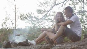 Lyckliga tonåringpar stekte korvar på rökig brasa i skogen stock video