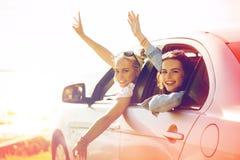 Lyckliga tonårs- flickor eller kvinnor i bil på sjösidan royaltyfri foto
