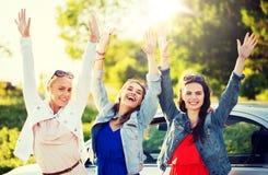 Lyckliga tonårs- flickor eller kvinnor near bilen på sjösidan royaltyfria bilder