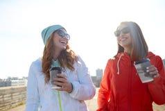 Lyckliga tonårs- flickor med kaffekoppar på gatan Royaltyfria Bilder