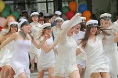 Lyckliga tonårs- flickor som bär avläggande av examen, caps spring ut från sch Arkivfoton