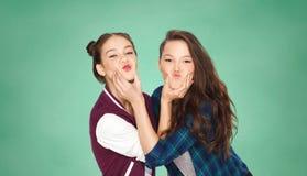 Lyckliga tonårs- flickor som har gyckel över grönt bräde arkivfoton