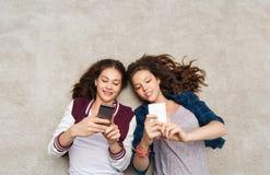 Lyckliga tonårs- flickor som ligger på golv med smartphonen Royaltyfri Fotografi