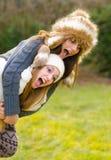 Lyckliga tonårs- flickor som rider på ryggen i naturen Royaltyfria Bilder