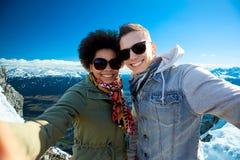 Lyckliga tonårs- par som tar selfie över berg Royaltyfri Fotografi