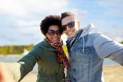 Lyckliga tonårs- par som tar selfie över stranden royaltyfria bilder