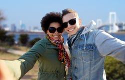 Lyckliga tonårs- par som tar selfie i tokyo Royaltyfria Foton