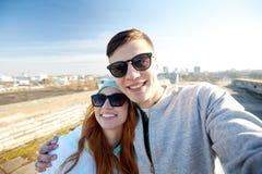 Lyckliga tonårs- par som tar selfie på stadsgatan arkivfoton