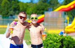 Lyckliga tonårs- pojkar som visar tummar upp i vatten, parkerar Royaltyfri Foto
