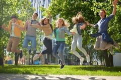 Lyckliga tonårs- studenter eller vänner som utomhus hoppar Royaltyfri Foto