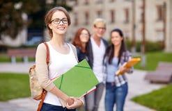 Lyckliga tonårs- studenter med skolamappar arkivbild