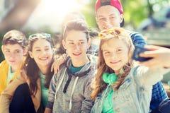 Lyckliga tonårs- studenter som tar selfie vid smartphonen royaltyfri foto