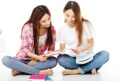 lyckliga tonårs- studentflickor som håller ögonen på böckerna Arkivbild