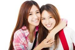 Lyckliga tonårs- studentflickor som isoleras på vit Arkivbild