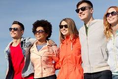 Lyckliga tonårs- vänner i skuggor som talar på gatan royaltyfri foto