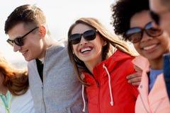 Lyckliga tonårs- vänner i skuggor som talar på gatan royaltyfri bild