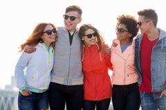 Lyckliga tonårs- vänner i skuggor som talar på gatan arkivfoto
