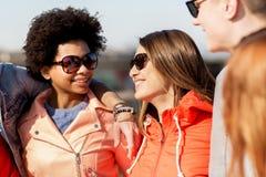Lyckliga tonårs- vänner i skuggor som talar på gatan royaltyfri fotografi