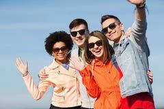 Lyckliga tonårs- vänner i skuggor som vinkar händer Arkivfoton