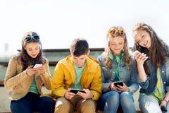 Lyckliga tonårs- vänner med smartphones utomhus arkivbilder