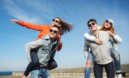 Lyckliga tonårs- vänner som har roligt utomhus Arkivfoto