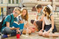 Lyckliga 4 ton?rs- v?nner eller h?gstadiumstudenter har gyckel och att tala som l?ser telefonen, boken Kamratskap och folkbegrepp royaltyfri bild
