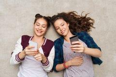 Lyckliga tonårs- flickor som ligger på golv med smartphonen Royaltyfria Foton