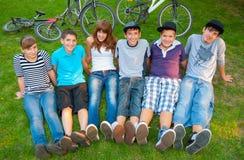 Lyckliga tonårs- pojkar och flickor som vilar i gräset Royaltyfri Bild