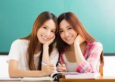 lyckliga tonårs- studentflickor i klassrum Arkivfoto