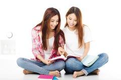 lyckliga tonårs- studentflickor som håller ögonen på böckerna Royaltyfri Foto