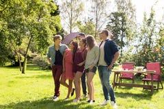 Lyckliga tonårs- vänner som talar på sommarträdgården Arkivfoton