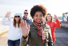 Lyckliga tonårs- vänner som vinkar händer på stadsgatan Arkivbild
