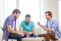 Lyckliga tre manliga vänner som hemma spelar poker Fotografering för Bildbyråer