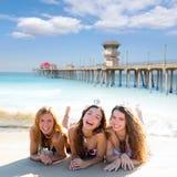 Lyckliga tre vänflickor som ligger på stranden, sandpapprar smil Arkivbild