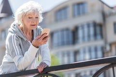 Lyckliga trevliga äldre kvinnan som den har, kopplar av tid, medan öva utomhus Arkivbild
