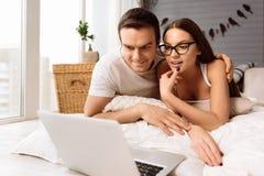 Lyckliga trevliga par som ser bärbar datorskärmen arkivbild