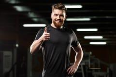 Lyckliga tummar för sportmanvisning gör en gest upp royaltyfria foton