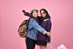 Lyckliga turist- flickvänner som tillsammans möter och kramar på flygplatsen, ung asiatisk handelsresande som har gyckel fotografering för bildbyråer
