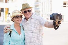 Lyckliga turist- par som tar en selfie i staden Arkivbild