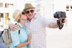 Lyckliga turist- par som tar en selfie i staden Royaltyfri Bild