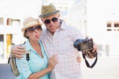 Lyckliga turist- par som tar en selfie i staden Royaltyfri Foto
