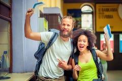 Lyckliga turister som rymmer biljetter för ferie royaltyfri fotografi