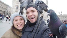 Lyckliga turister som tar en självstående med duvor som är främsta av Duomodomkyrkan, Milan lager videofilmer