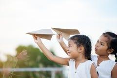 Lyckliga två asiatiska barnflickor som spelar med det pappers- flygplanet för leksak Arkivbilder