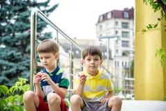 Lyckliga två broderungar som spelar med leksakflygplanet på varm sommardag Pojkar ser skalakopian av nivån Bästa barndom och lopp royaltyfri foto