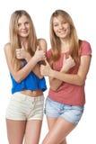 Lyckliga två flickavänner som gör en gest upp tummar arkivbilder