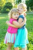 Lyckliga två små systrar har en vila på naturen royaltyfri bild