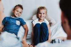 Lyckliga två ungar som framme sitter på säng av föräldrar royaltyfria bilder