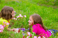 Lyckliga tvilling- systerflickor som spelar på våren, blommar ängen royaltyfri foto