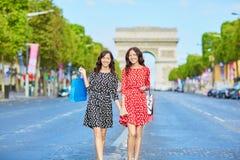 Lyckliga tvilling- systrar som gör shopping på ferier i Frankrike Royaltyfria Bilder